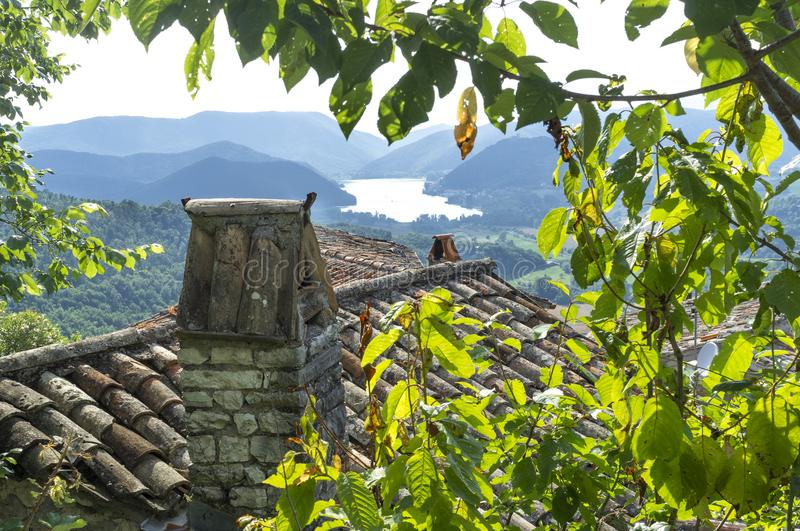 Red tile roofs with chimney. In the distance a lake in the mountains royalty free stock image