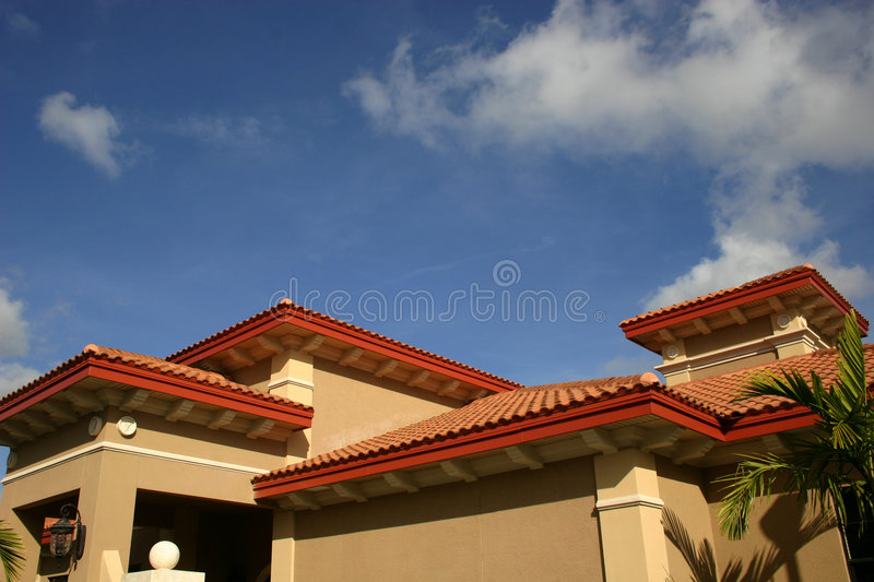 Red tiled roofs. Against bright blue sky and white clouds stock photography