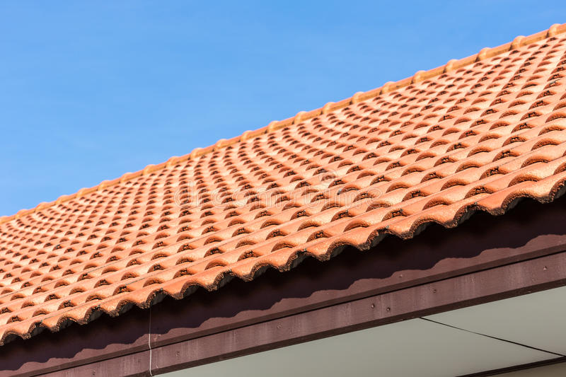 Red tiles roof and blue sky background stock photography