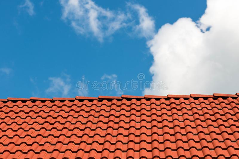 Red tiles on rooftop, beautiful blue sky with white clouds. In the background royalty free stock image