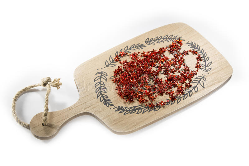 Red tinsel of the stars for the Christmas tree. On a wooden tray royalty free stock image
