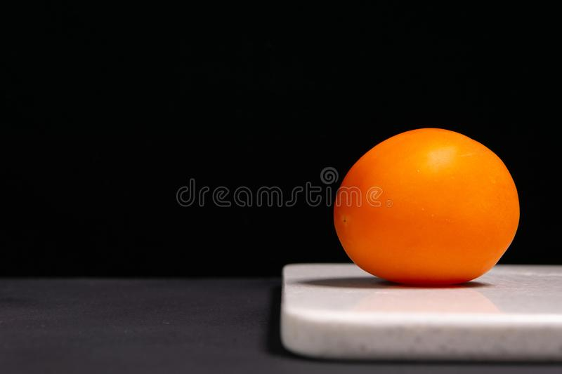 Red tomato on a black and gray background stock photography