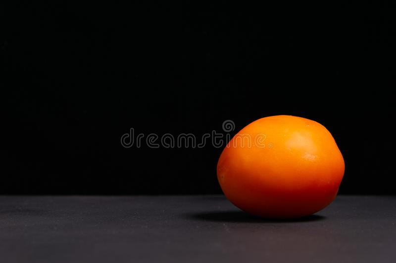 Red tomato on a black and gray background royalty free stock image