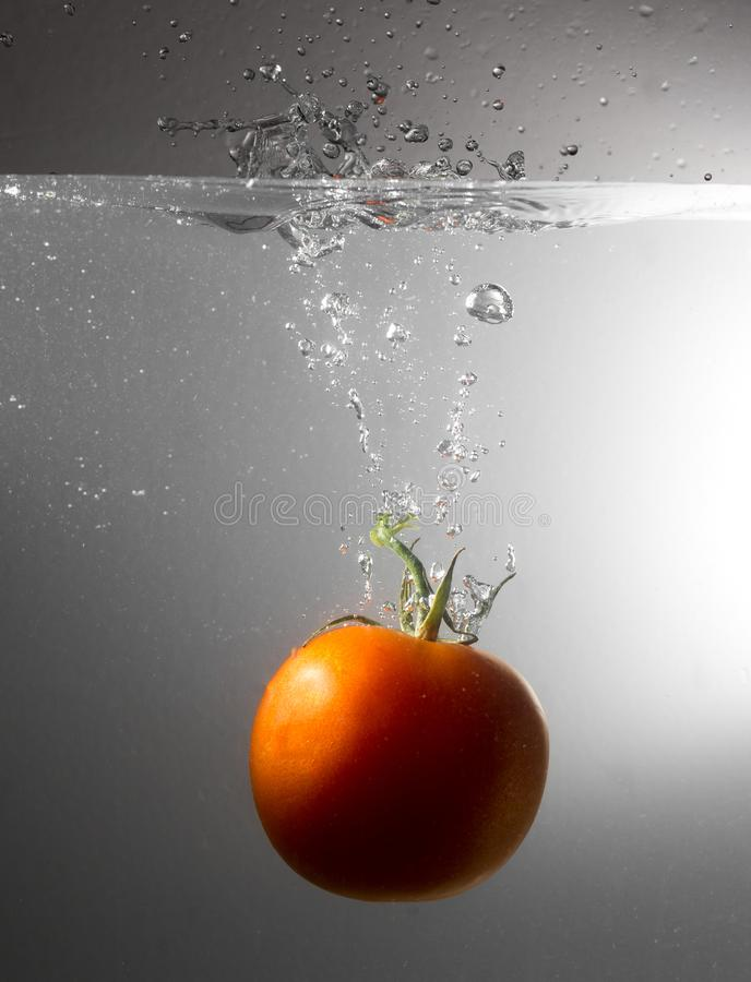 Red tomato drops in water with a spray stock image