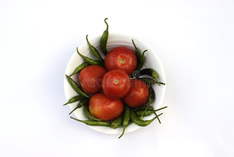 Red tomato and green chili pepper, essential vegetables for mexican food stock images