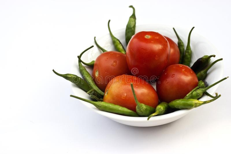 Red tomato and green chili pepper, essential vegetables for mexican food royalty free stock photos