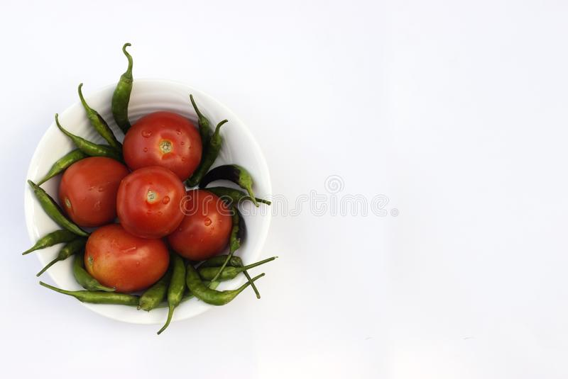Red tomato and green chili pepper, essential vegetables for mexican food stock photos