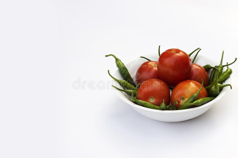 Red tomato and green chili pepper, essential vegetables for mexican food royalty free stock images