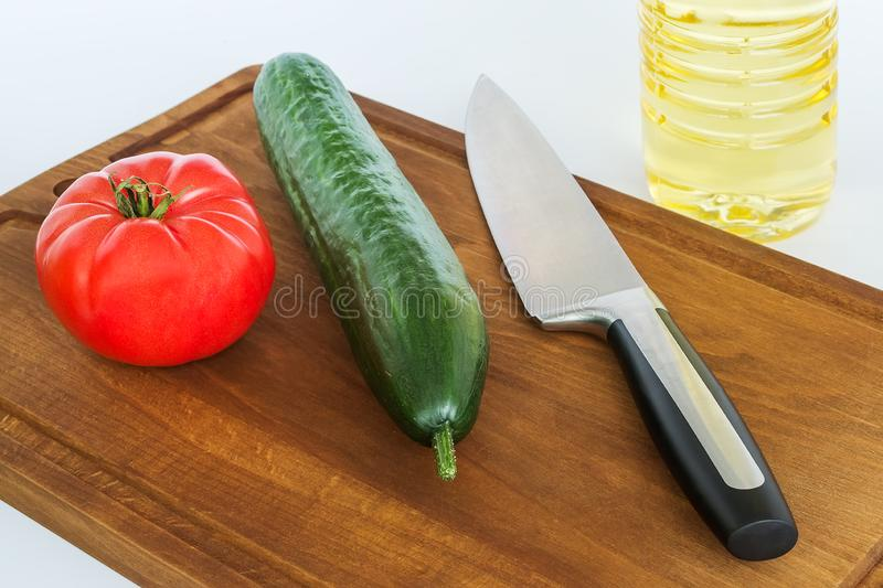 Red tomato, green cucumber and professional chef kitchen knife on a brown cutting board. Concept of healthy eating, vegetarian stock images
