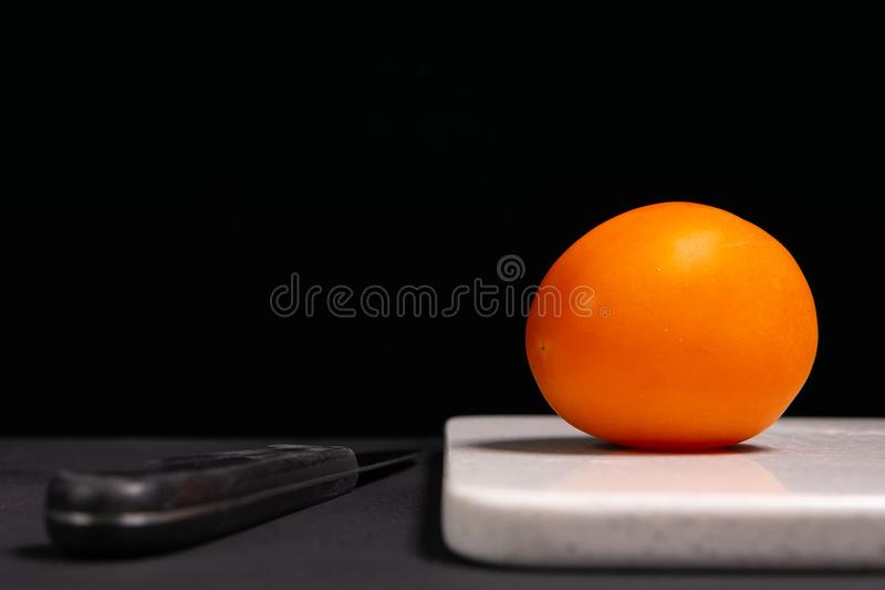 Red tomato and knife on a black background stock photography