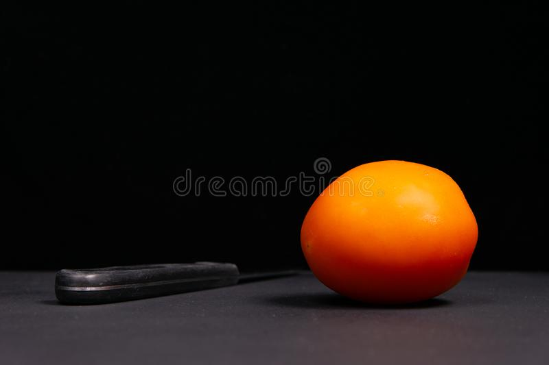 Red tomato and knife on a black background royalty free stock photos