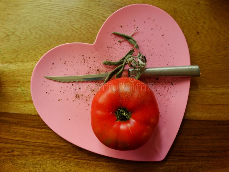 Red tomato on pink heart royalty free stock photos