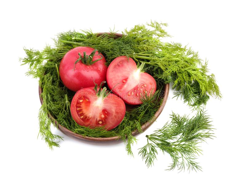 Red tomatoes with fresh dill in a wooden basket, isolated on a white background. Vegetarian food concept. stock photo