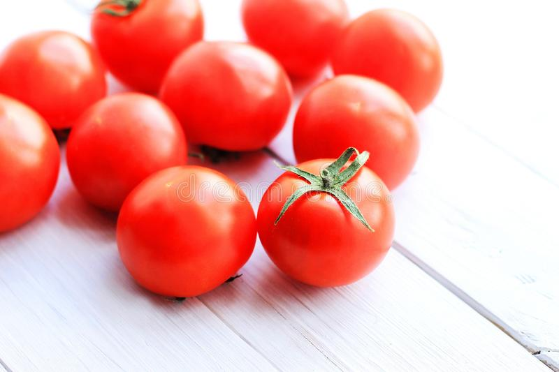 Red tomatoes on a light wooden background royalty free stock images