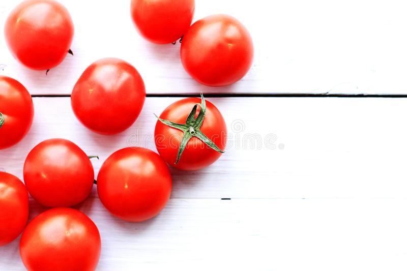 Red tomatoes on a light wooden background royalty free stock image