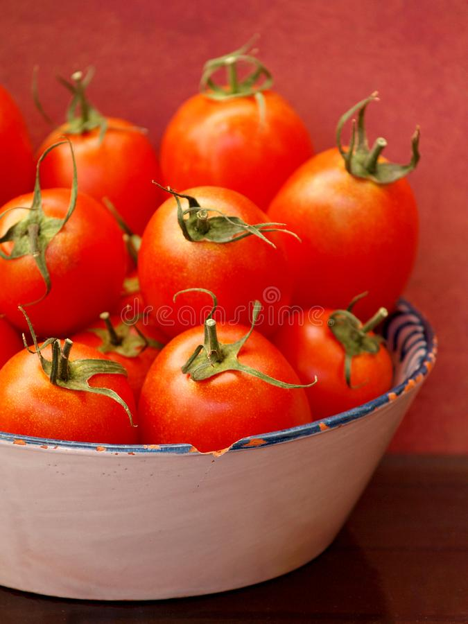 Red tomatoes in old tray. Stillife red tomatoes in old tray with brown and red abstract background royalty free stock photos