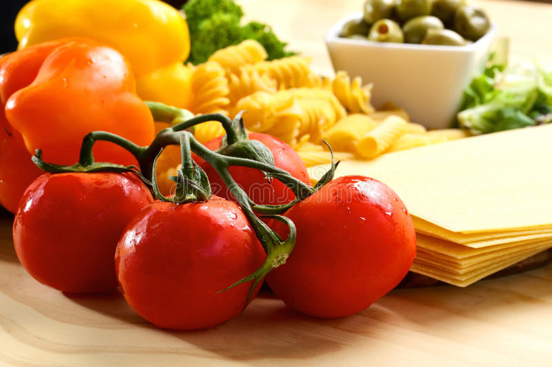Red tomatoes and variety of uncooced italian pasta stock images