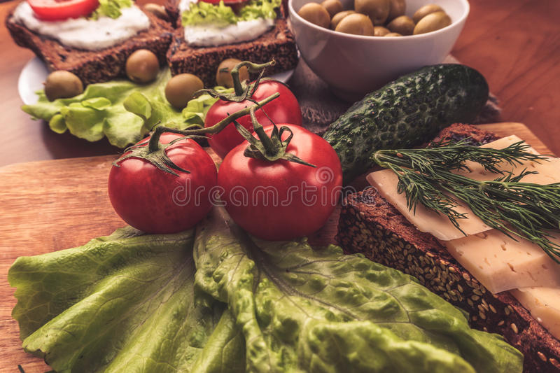 Red tomatoes on wooden board and bread with sauce, olives in bowl on kitchen stock photo