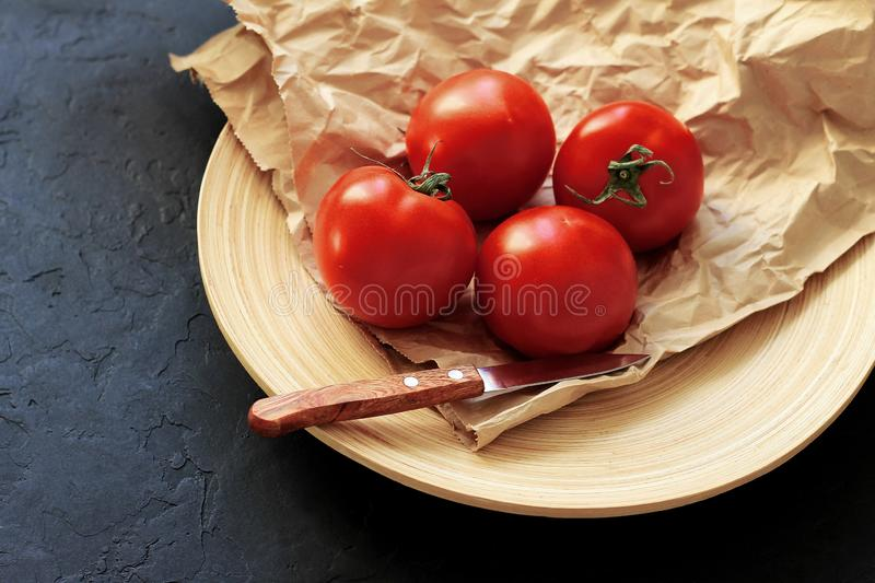 Red tomatoes on a wooden plate on a dark background royalty free stock photography