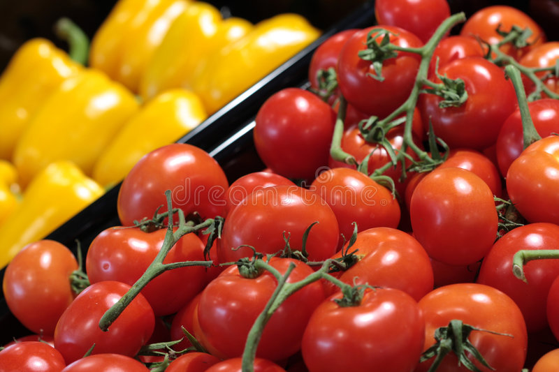 Red tomatos and yellow peppers stock image