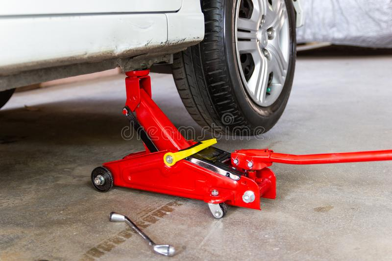 Red tool jack lift car for repair check Maintenance stock image