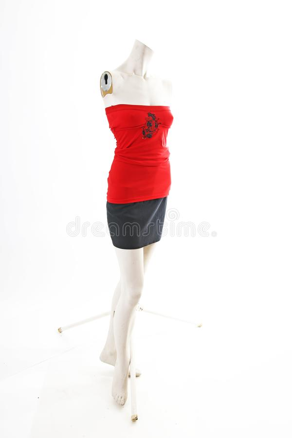 Red top with black skirt on mannequin full body shop display. Woman fashion styles, clothes on white studio background. stock image