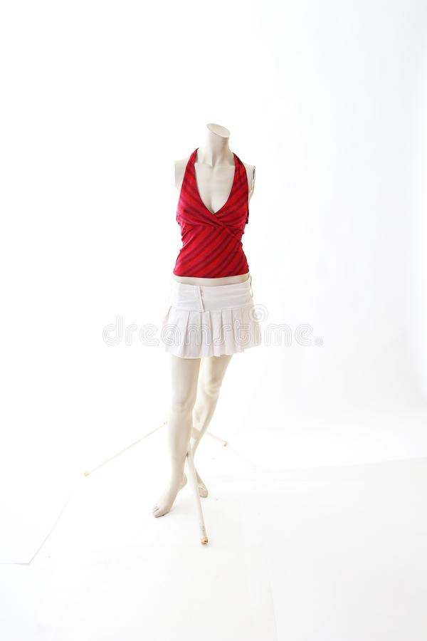 Red top and white mini skirt on mannequin full body shop display. Woman fashion styles, clothes on white studio background.  royalty free stock image