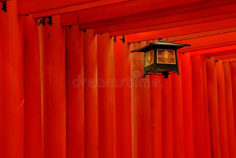 Red torii gates and lantern. Detail of red torii gates and a lantern stock photos
