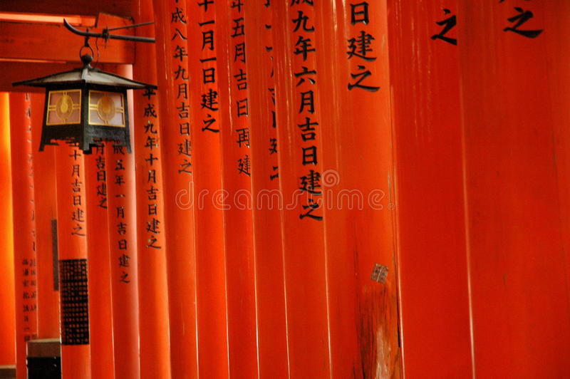 Red torii gates and lantern. Detail of red torii gates with inscription and a lantern at Fushimi Inari Shrine, Kyoto, Japan stock images