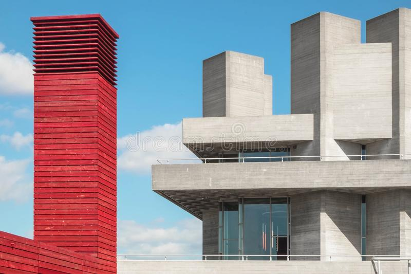 Red tower made of wood beside a concrete building with concrete towers and blue sky with white clouds. In Southbank, London stock photography
