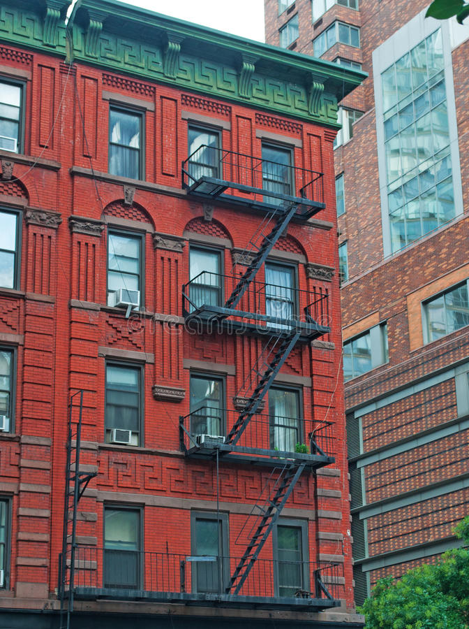 Red townhouse with emergency stairs in Soho, New York, skyline. New York City, Nyc, the Big Apple, Manhattan, United States of America, Usa: red townhouse with stock image