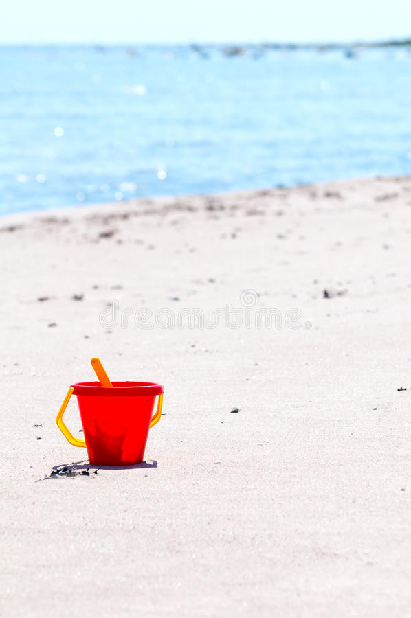 Red toy bucket on the beach stock photo