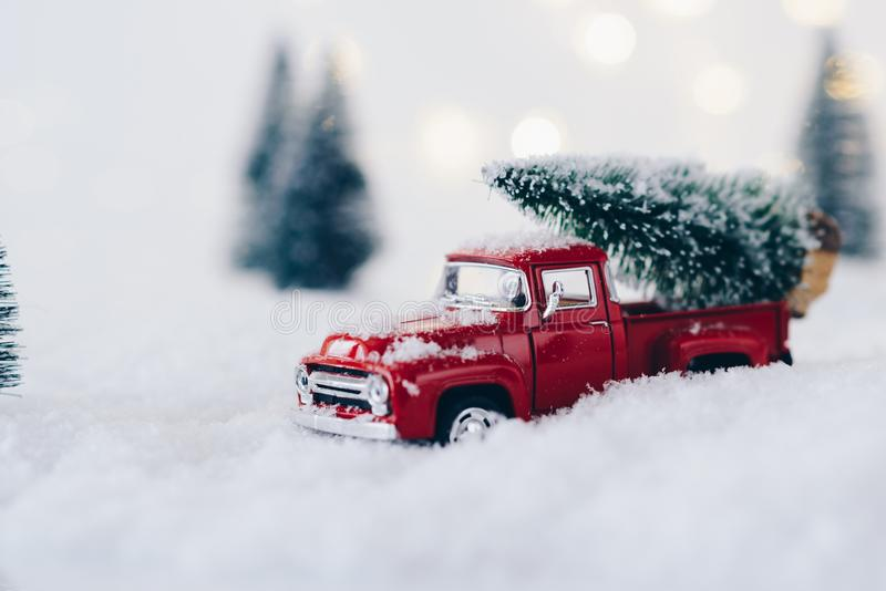 Red toy car carrying Christmas tree. Christmas card stock images