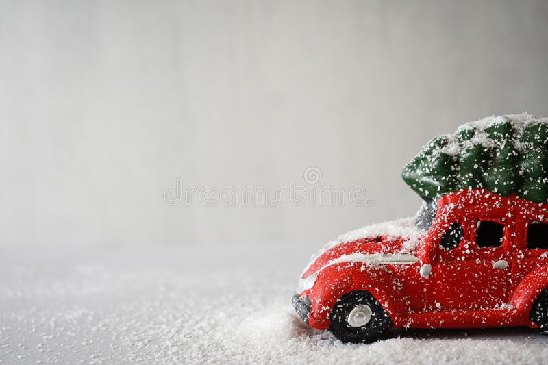 Red toy car with a Christmas tree on the roof, on a gray background. Place for text. Christmas composition. Red toy car with a Christmas tree on the roof in the stock images