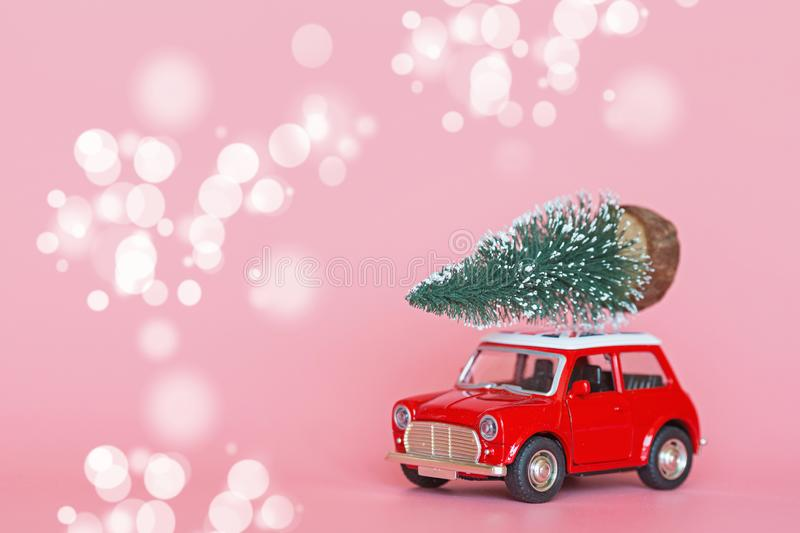 Red toy car with a christmas tree on the roof on pink paper background. Winter delivery, xmas, happy new year 2020 celebration stock images