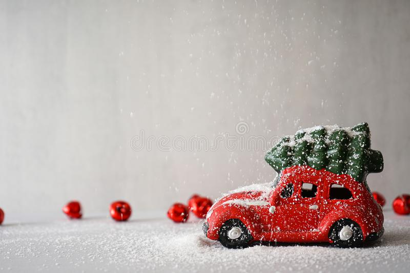 Red toy car with a Christmas tree on the roof in the snow, on a gray background with red New Year`s toys. Place for text.  stock photos