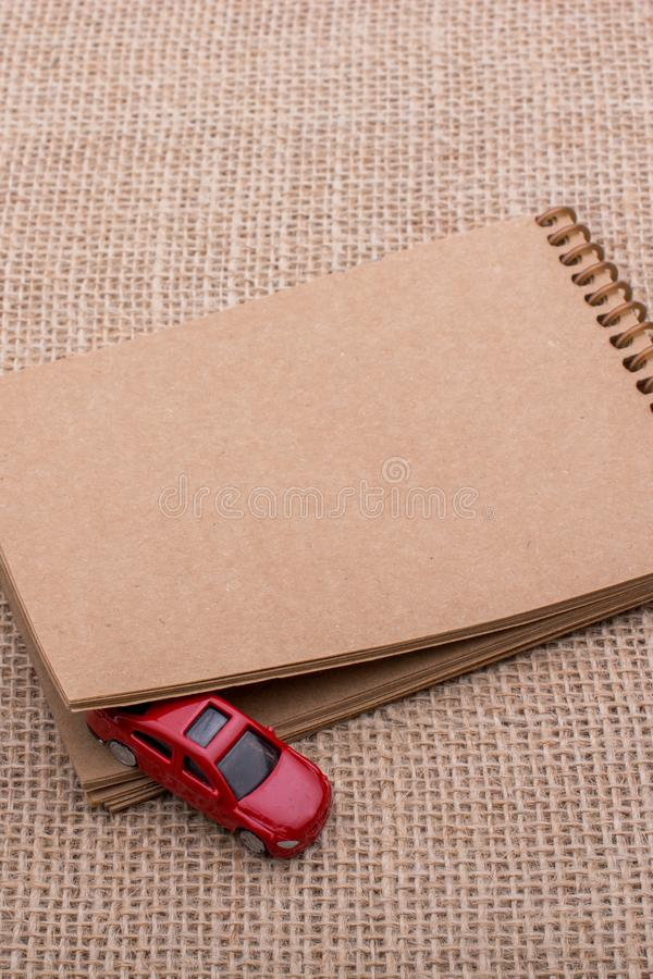 Red toy car out of a notebook on a canvas. Red toy car coming out of a notebook on a linen canvas stock image