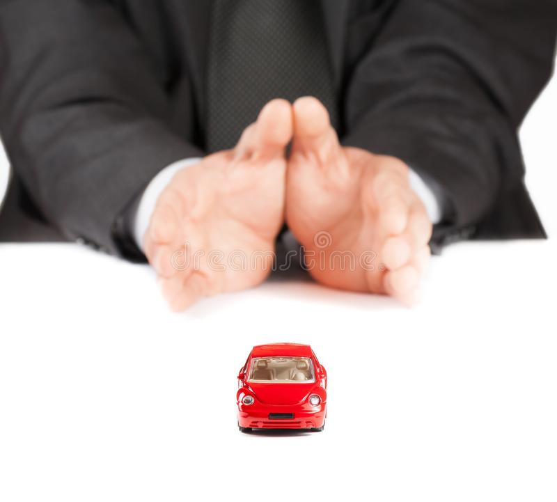 Red toy car in front of businessman, concept for insurance, buying, renting, fuel or service and repair costs. Red toy car in front of businessman on white table royalty free stock images