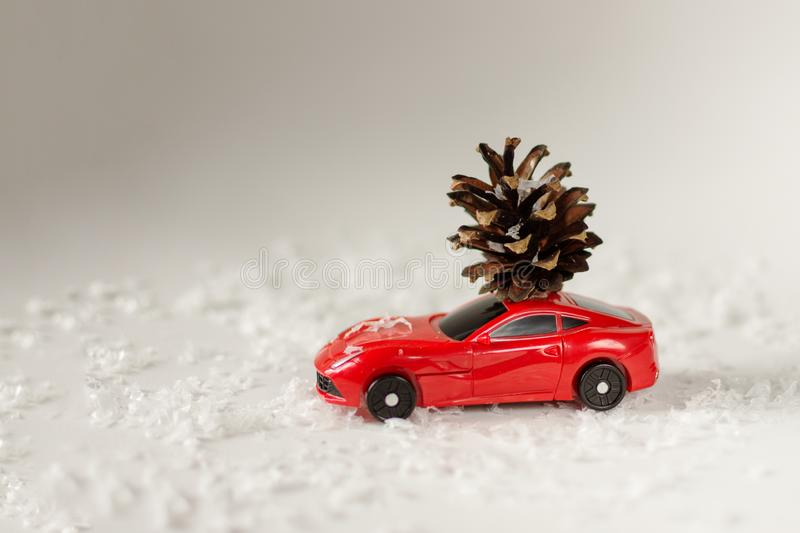 Toy car with pine cone on a white snow background. Red toy car with pine cone on a white snow background . Christmas card concept. Copy space royalty free stock photography