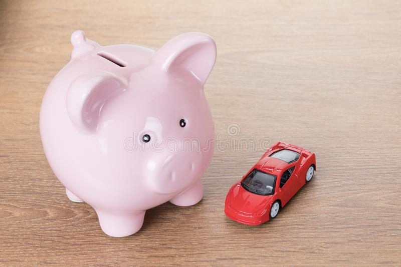 Red toy car with a pink piggy bank. On a wooden table in a concept of saving for a dream vehicle or of the cost of maintenance and repairs stock photography