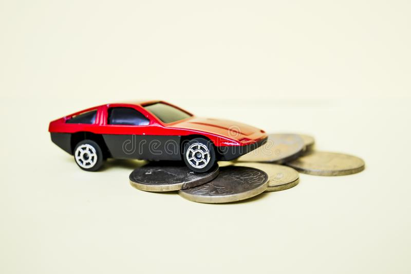 Red toy car rides up a stack of coins.  stock images