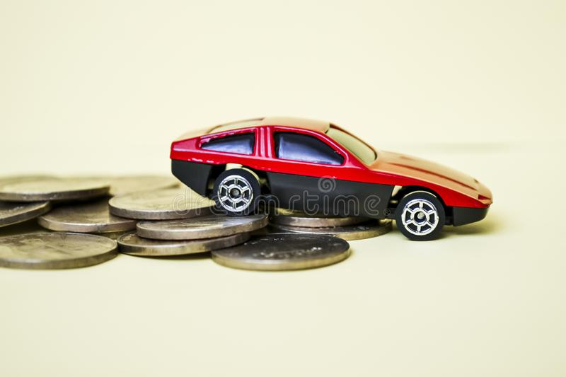 Red toy car rides up a stack of coins.  stock photography