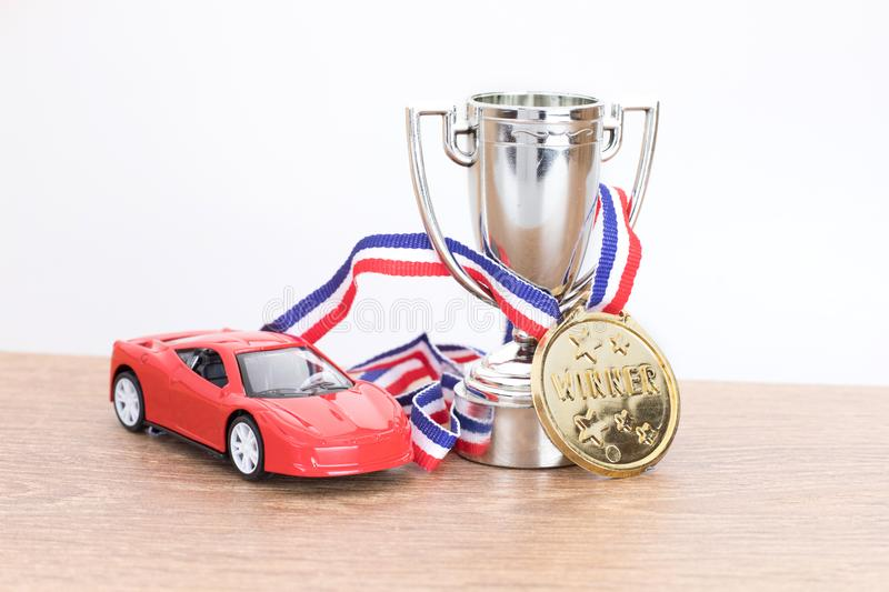 Red toy car with silver sporting trophy royalty free stock image