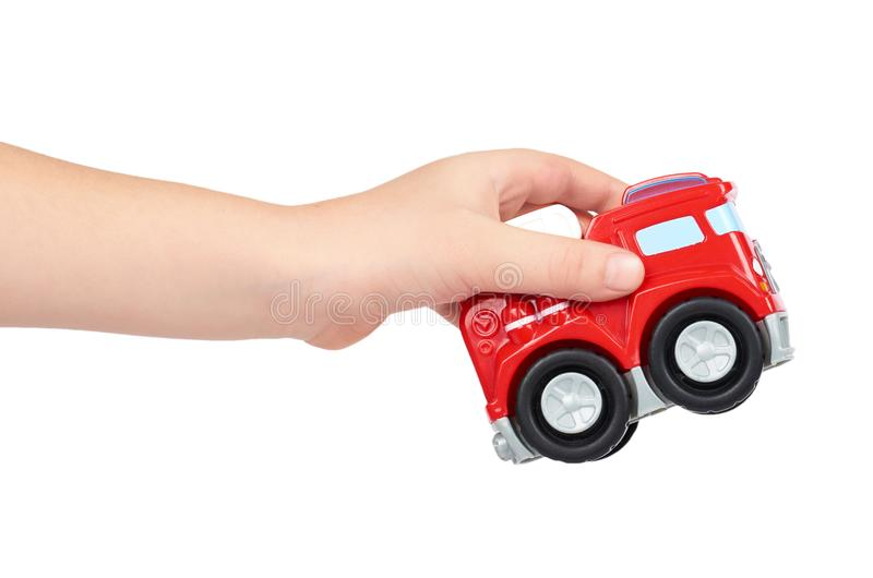 Red toy firefighter car with kid hand, isolated on white background, fire truck engine stock photo