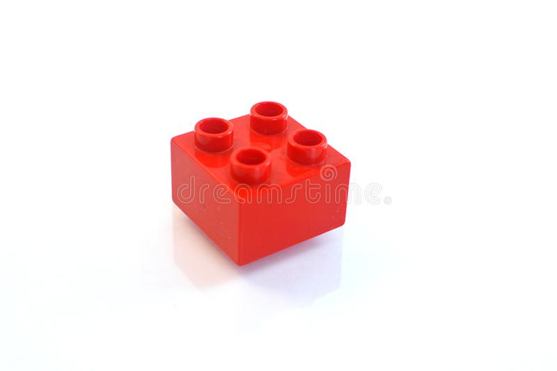 Red toy lego duplo piece. Lego building bricks in different colors over white background piece royalty free stock images