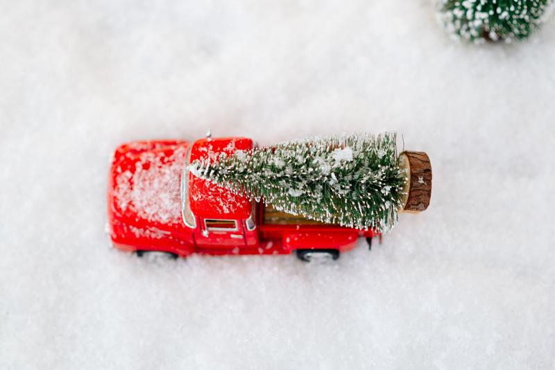 Red toy pickup car carrying Christmas tree. In the snow royalty free stock photography