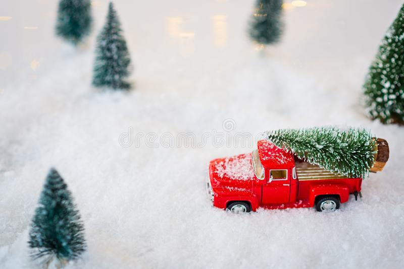 Red toy pickup car carrying Christmas tree. In the snow royalty free stock photos