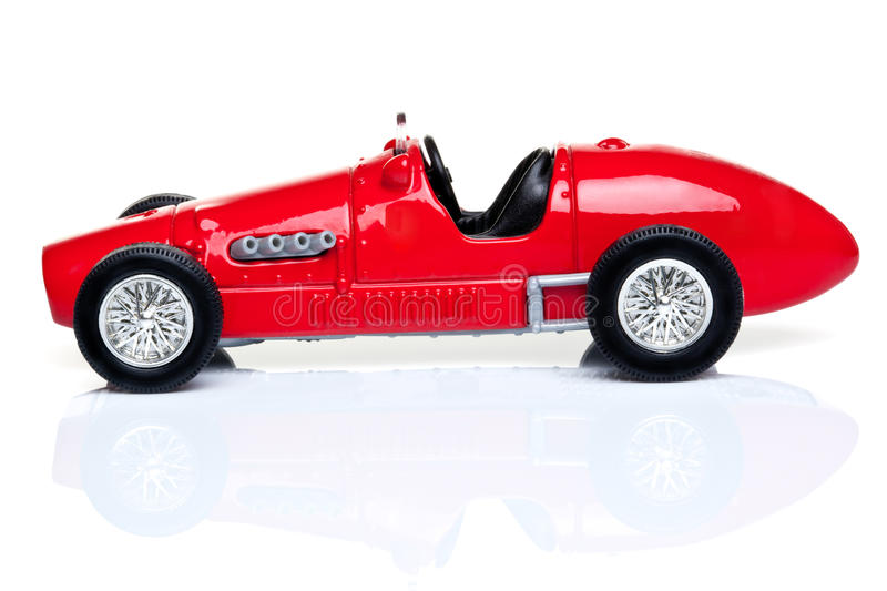 Red toy racing car. Old fashioned red toy racing car on a white background with reflection royalty free stock photos
