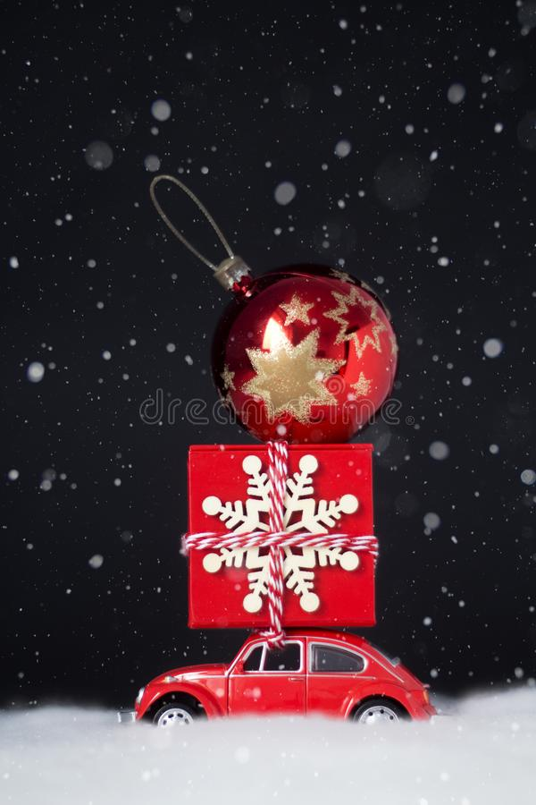 Red toy retro car carries on a roof a Christmas gift and Christmas ball stock photography