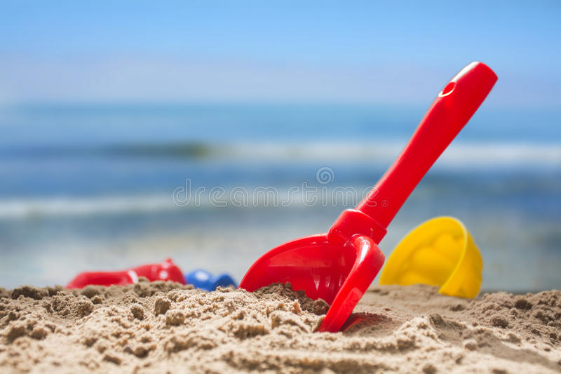 red toy shovel and plastic molds in the sand at the beach, concept of summer vacation with children at sea, copy space stock photography